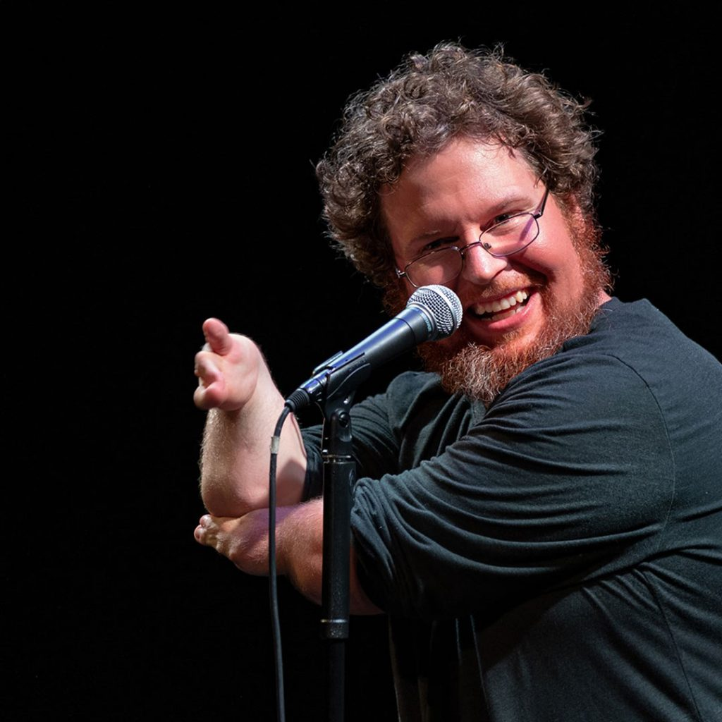 Ryan Niemiller at a microphone on stage doing a comedy act.