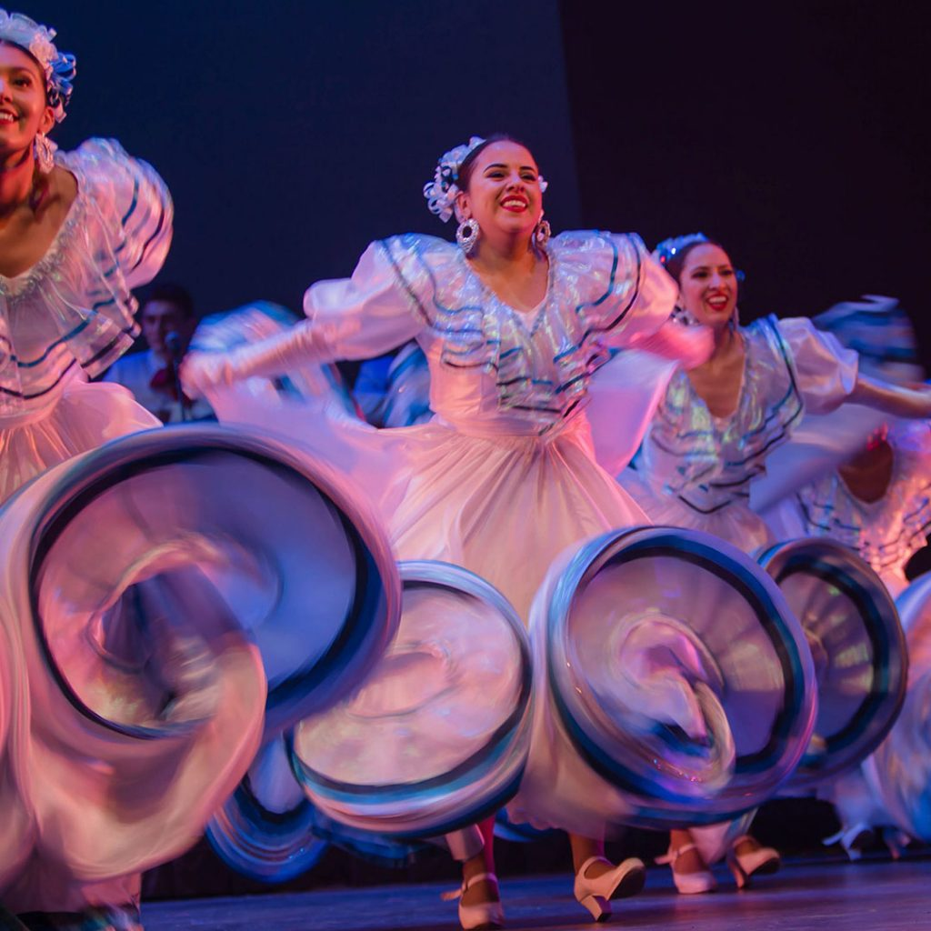A group of Flamenco dancers in colorful dresses on stage
