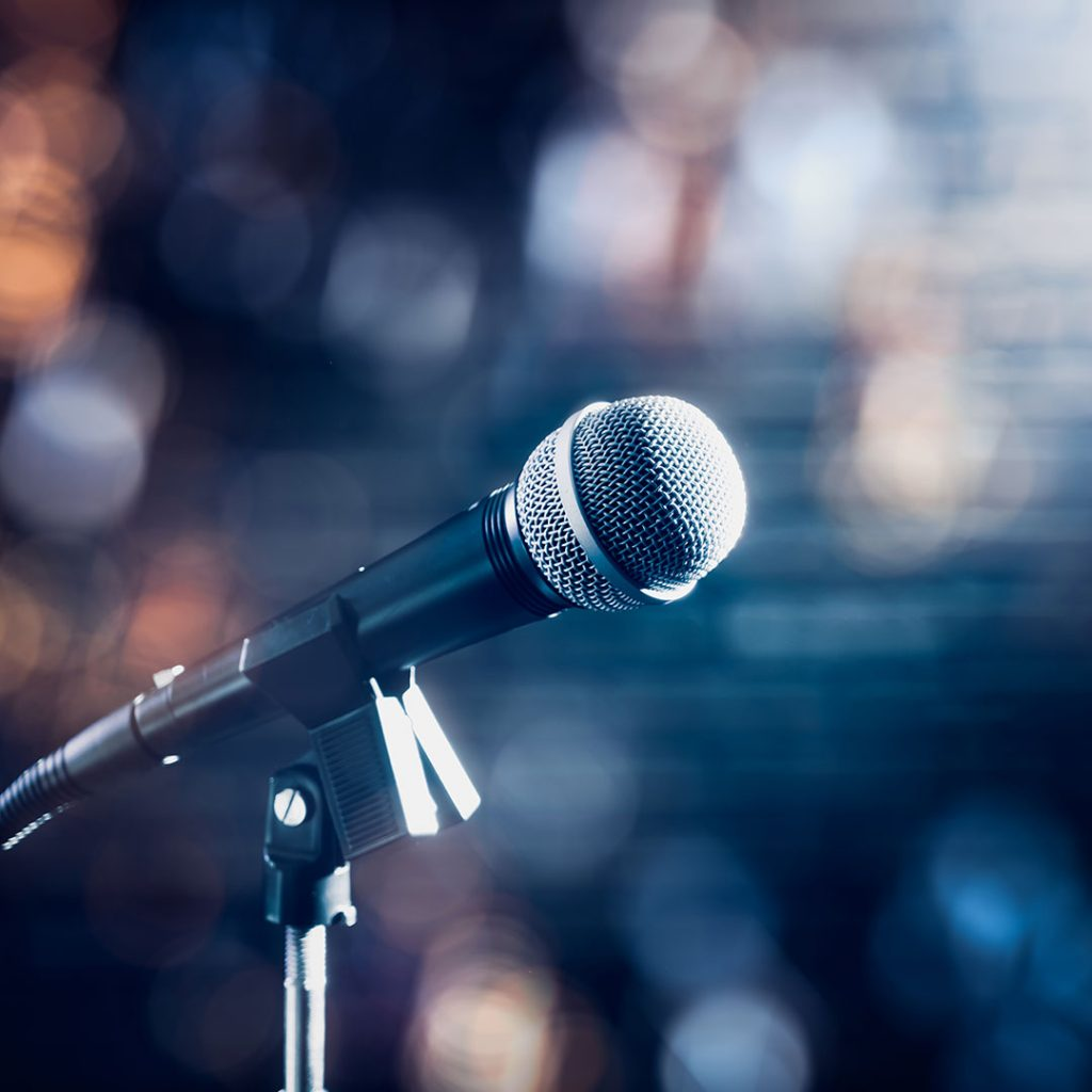 Microphone on a stand-up comedy stage with colorful bokeh.